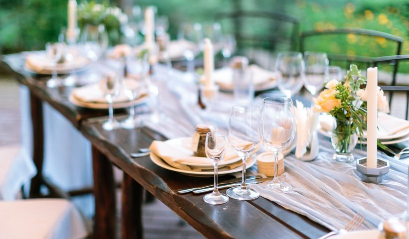 fest, dinner, tradition concept. long oaken table served for celebration with silverware, dishes and transparent dazzling glasses, flowers and candles in interesting holders in form of octagonal